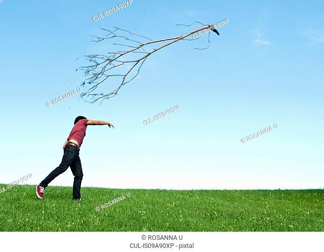 Teenage boy throwing branch in park