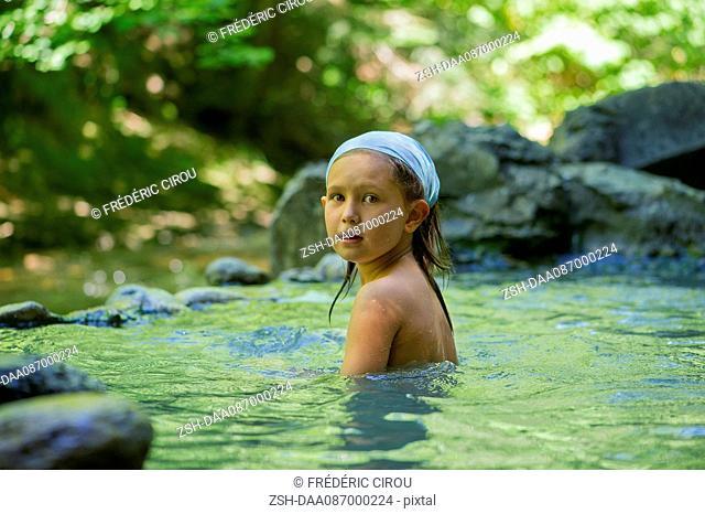 Girl bathing in natural pool