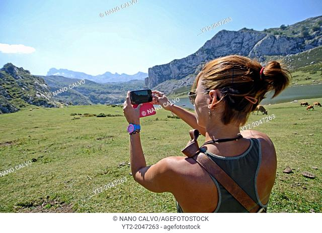 Young woman takes a photo of the Covadonga Lakes (Lagos de Covadonga) with her mobile phone