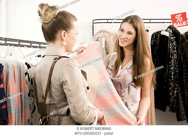 Sales girl with customer in fashion store