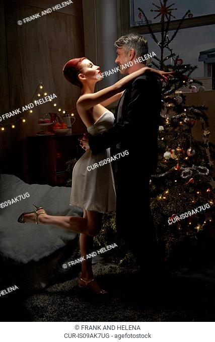 Husband and wife dancing by Christmas tree