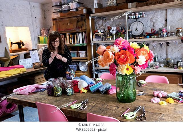 Woman standing in a workshop, bunch of colourful handcrafted fabric flowers in a vase on a table