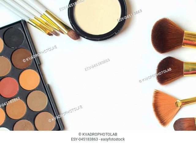 makeup brushes, eyeshadow and powder isolated on white background