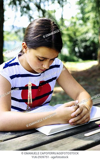 girl reads outdoors in the park