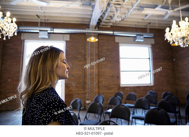 Serene businesswoman with eyes closed in conference room