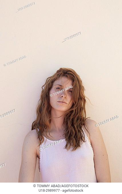 Half-length portrait of young redhead woman leaning against a white wall
