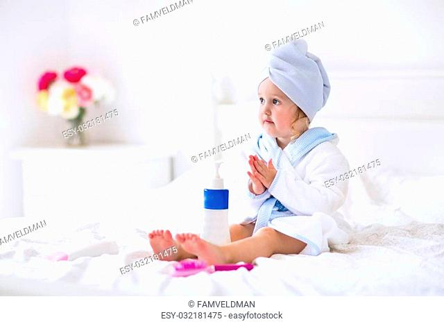 Child after bath. Cute little girl with wet curly hair wearing a bathrobe and head towel sitting on a white bed using lotion and brush