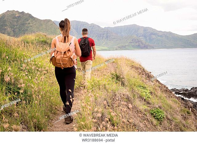 Couple with backpack walking in countryside
