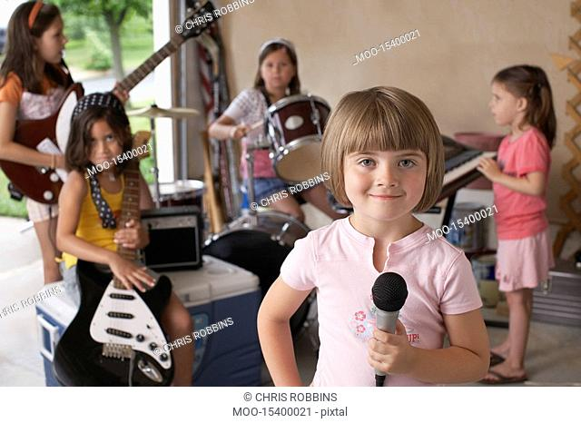 Group of girls 7-9 with instruments in garage