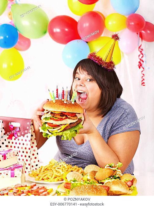Woman eating hamburger at birthday. Isolated