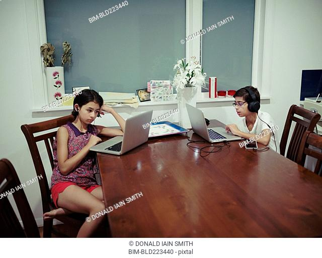 Mixed Race brother and sister using laptops at table