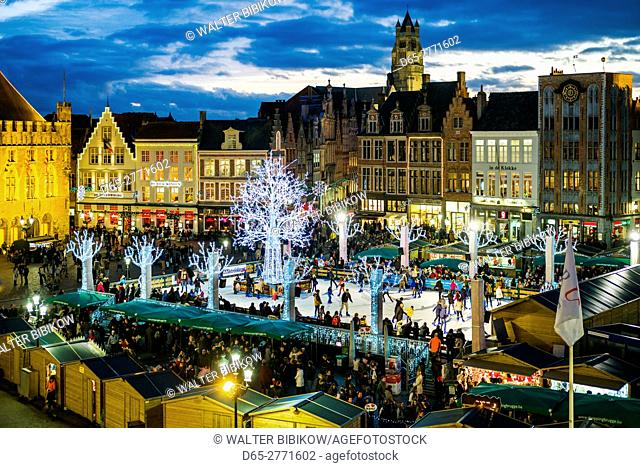 Belgium, Bruges, The Markt, elevated view of main square buildings and winter ice skating rink, dusk