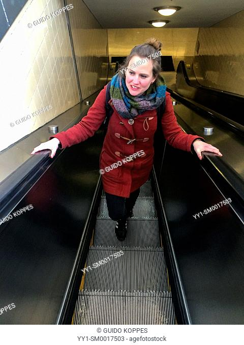 Newark, New Jersey, USA. Young, brunette woman using the escalator inside a railway station