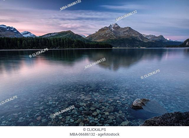 Dawn illuminates the peaks reflected in the calm waters of Lake Sils Engadine Canton of Graubünden Switzerland Europe
