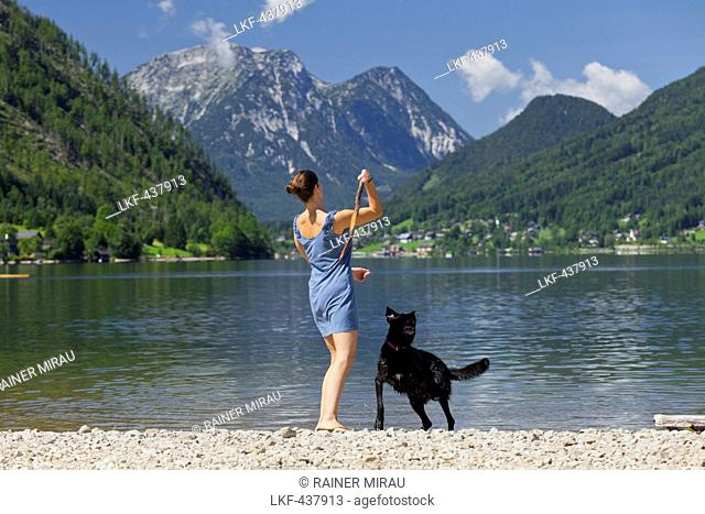 Woman playing with her dog on the shore of lake Grundlsee, Hoher Sarstein, Salzkammergut, Styria, Austria