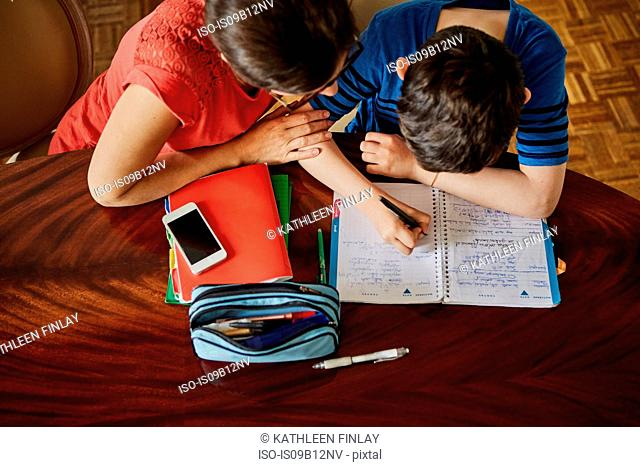 High angle view of mother at dining table helping son with homework