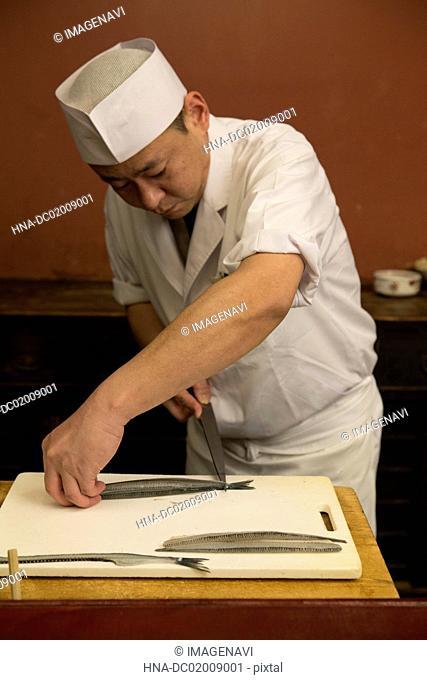 Japanese cook preparing fish