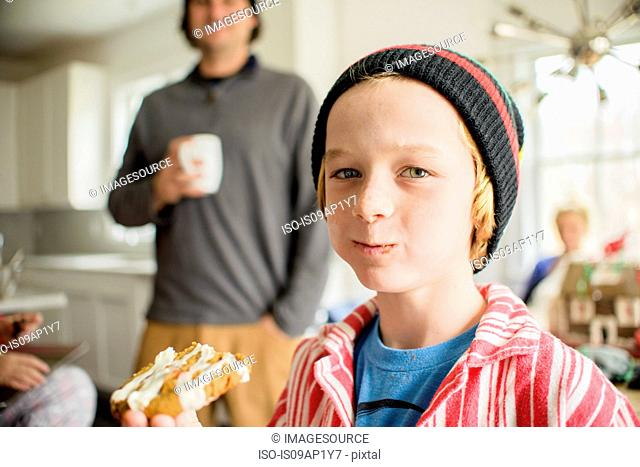 Portrait of boy eating cake in kitchen