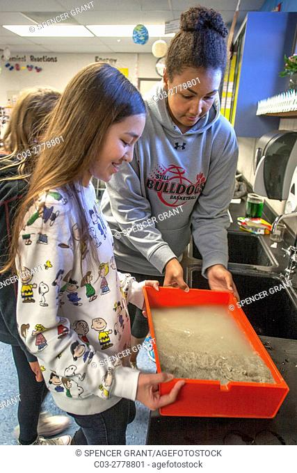 Caucasian and African American middle school science students in Mission Viejo, CA, use a tilted shallow plastic tray of sand to demonstrate the effect of...