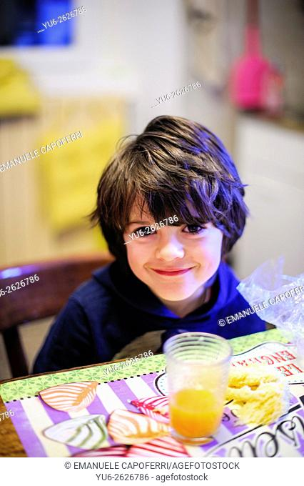 Boy at the kitchen table with a glass of orange juice in front