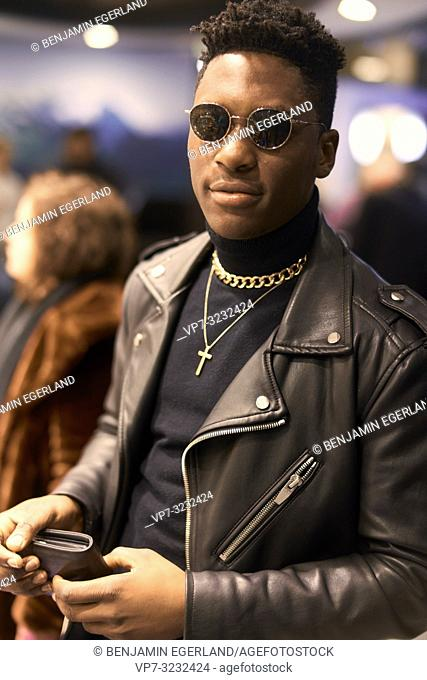 fancy young man holding wallet in hands in city between passersby, African descent, wearing sunglasses, leader jacket, jewellery, Christian cross, Munich