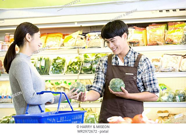 Smiling customer and employee at supermarket