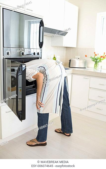 Rear view of woman looking into the oven in kitchen