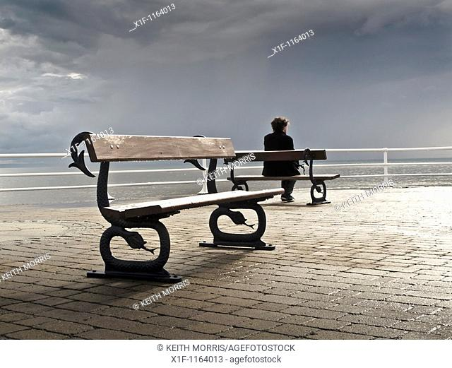 A man sitting alone on a bench on the promenade, grey overcast July summer afternoon, Aberystwyth Wales UK