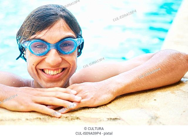 Portrait of young man wearing goggles in swimming pool