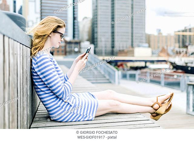 Young woman sitting at pier using mobile phone