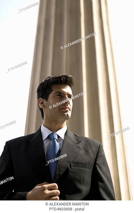 India, Businessman in suit and blue tie against sky and column