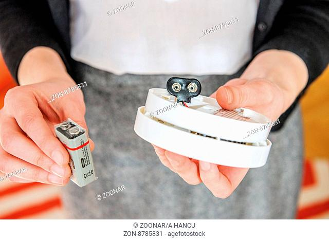 Woman installing 9 volt battery in smoke detector