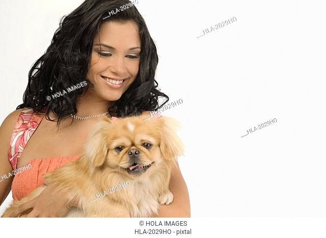 Close-up of a young woman carrying a Pomeranian dog