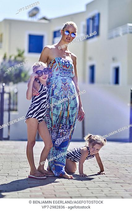 mother with two playful daughters in summer sun. Wearing sunglasses. Australian ethnicity