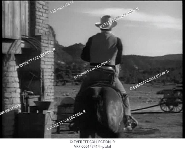 Rear view of cowboy riding towards mountains