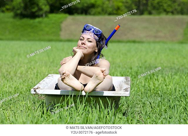 Woman with Diving Mask Sitting in a Bathtub on a Green Field with Grass in Locarno, Switzerland