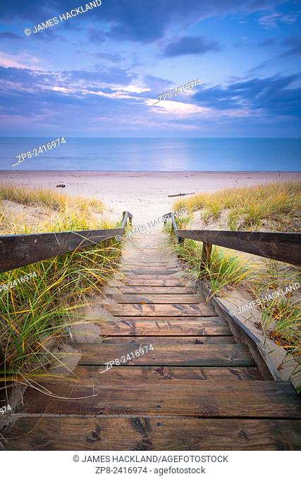 A staircase leading down grass covered dunes to a beach along the shore of Lake Huron. Pinery Provincial Park, Ontario, Canada