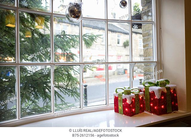 Window of a house with Christmas decorations. Christmas tree and gifts. Grassington, North Yorkshire, Yorkshire Dales, England, UK, Europe