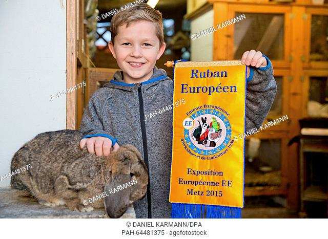 Tim Behringer, Junior European rabbit breeding champion, poses with a German Kleinwidder rabbit and pennant of the 2015 European Championships held in Metz
