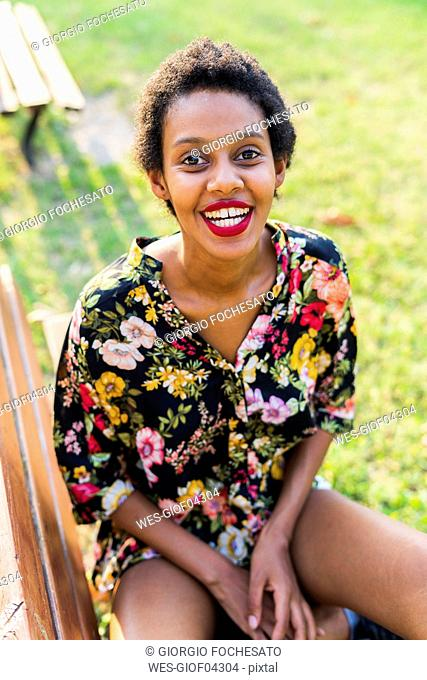 Portrait of laughing young woman sitting on bench in a park