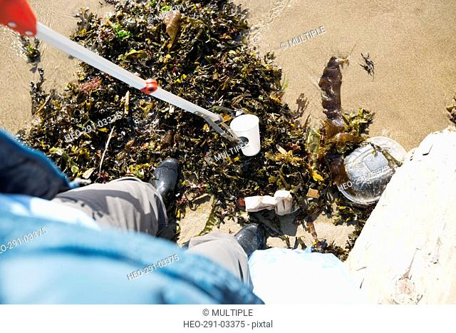 Personal perspective beach cleanup volunteer using claw to pick up litter