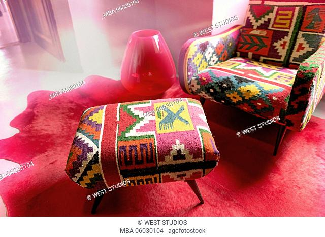 Padding armchair, ottoman, deocorative linen, patterned, red carpet, red lamp