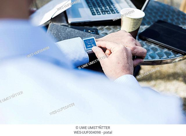 Businessman in cafeteria checking time, close up