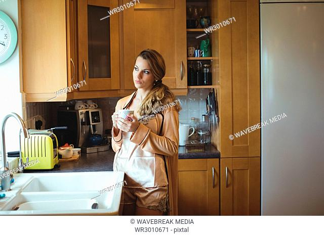 Thoughtful woman holding coffee cup in kitchen