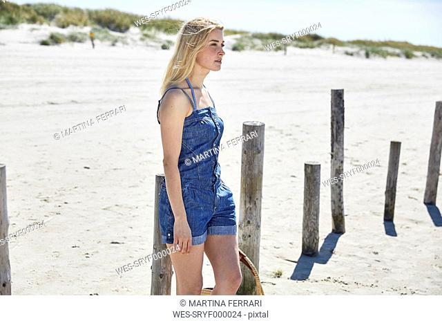 Young woman at wooden poles on the beach