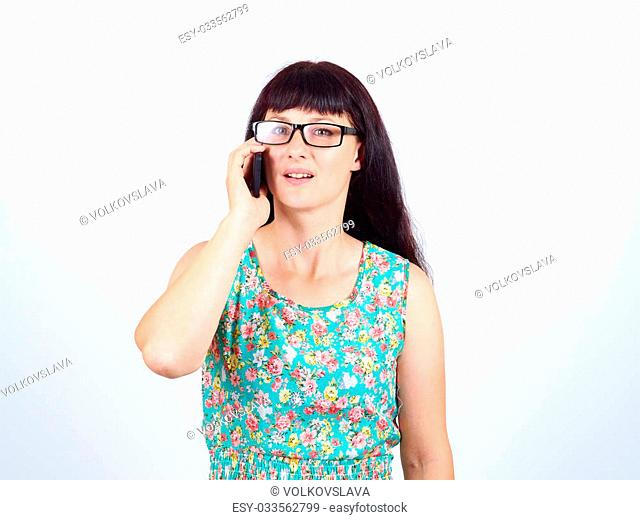 Young woman in glasses and a green dress talking on the phone