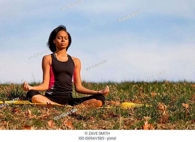 Young woman sitting on yoga mat, outdoors, in lotus position
