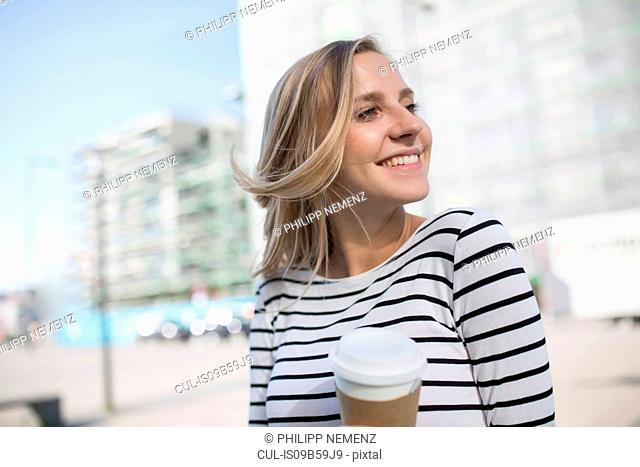 Young blond haired woman in city with takeaway coffee
