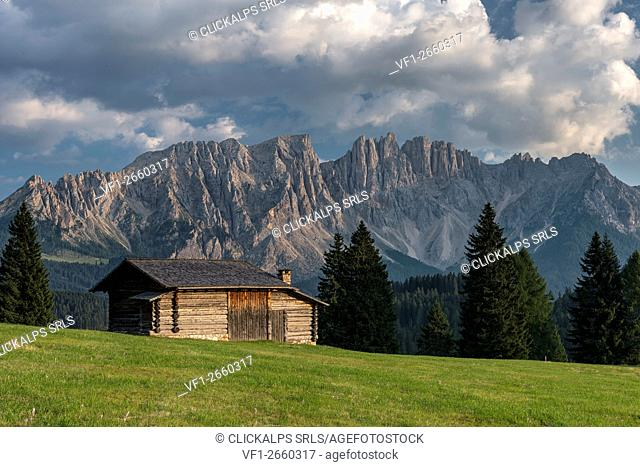 Carezza, Dolomites, South Tyrol, Italy. Mountain Hut in the pastures of Colbleggio. In the background the peaks of the Latemar