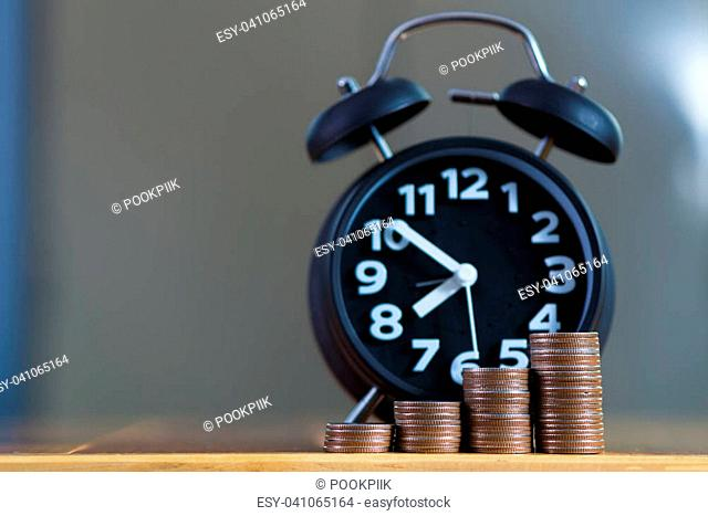 Alarm clock and step of coins stacks on working table, time for savings money concept, banking and business idea